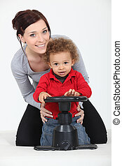 Woman and child playing with a toy steering wheel