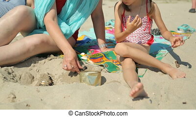 Woman and child playing with sand on beach