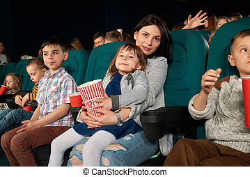 Woman and child sitting in movie theatre and posing at camera.