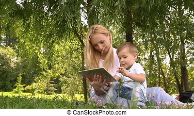 Woman and child using tablet computer. Slow motion. Young mother and little son spending day in the park.