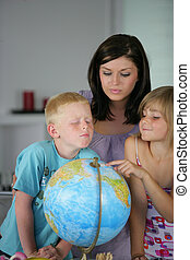 Woman and children looking at a globe