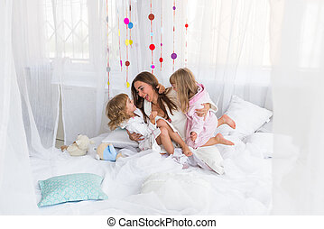 Woman and children on bed