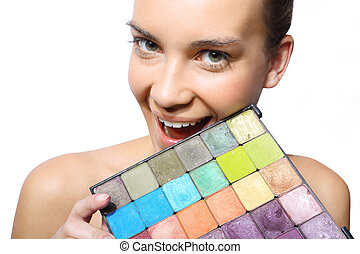 Beautiful woman with multicolored eyeshadow palette
