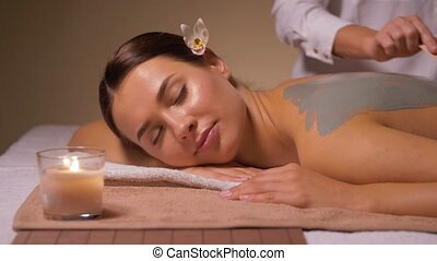 woman and cosmetologist applying clay mask in spa -...