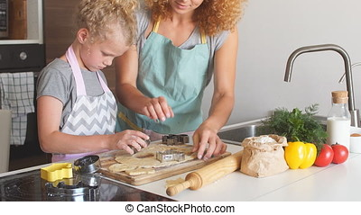 Woman and cute daughter cooking on kitchen, making dough for...