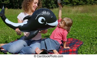 woman and daughter plays with toy sharks in summer field