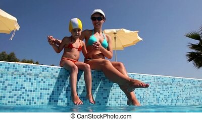 Woman and daughter, sits on pool border and wet feet