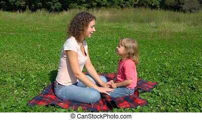 woman and daughter sits on summer field in park
