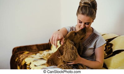 Woman and dog cocker spaniel. He strokes, touches, hugs,...