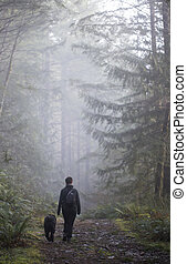 woman and dog on a foggy trail