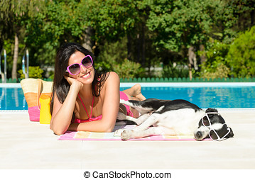 Woman and dog on summer at swimming pool