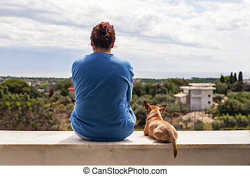 woman and dog watching landscape