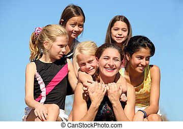 Woman and five girls - Woman laughing and five girls around...