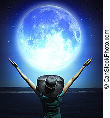 woman and full moon - Woman with raised hands facing a wave ...