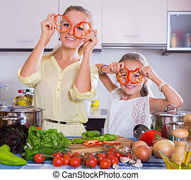 Woman and girl cooking veggies. - Cheerful young woman and ...