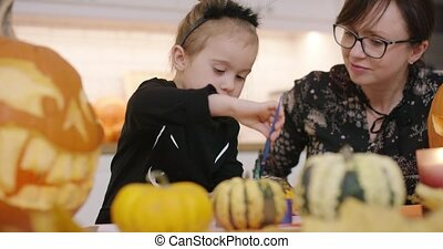 Woman and girl decorating pumpkins