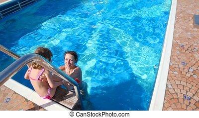 woman and girl having fun in swimming pool