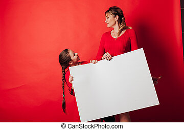 woman and girl hold a white sign against a red background