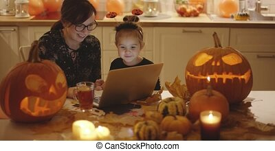 Woman and girl looking at laptop screen