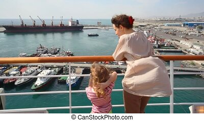 woman and girl looks at ships in sea port