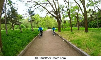Woman and girl on bicycles in the park. Slow motion.
