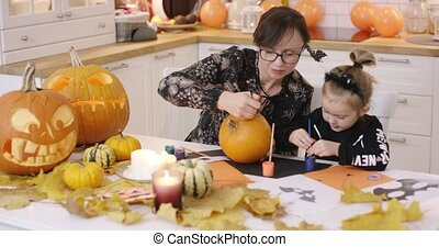 Woman and girl painting face on pumpkin - Woman in glasses...