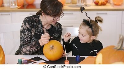 Woman and girl painting pumpkin - Woman in glasses and her...