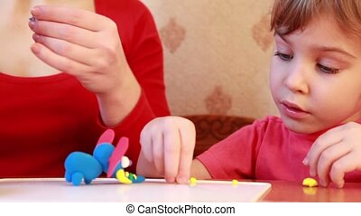 Woman and girl sculpts plasticine on table - Woman sculpt...