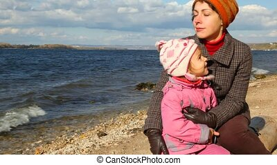 woman and little girl with coin sits on autumn sandy beach against river