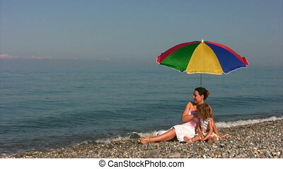 woman and girl sits under beach umbrella on coast