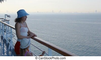 woman and girl stands on deck of cruise liner