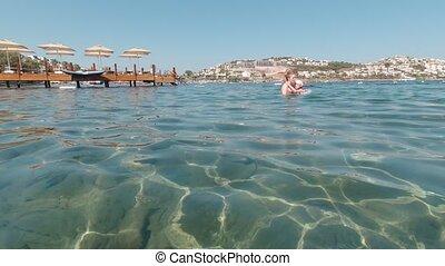 Woman and girl swim in sea coast of Turkey