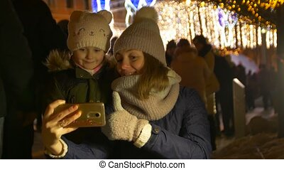 Woman And Girl Take A Christmas Selfie - Mother and daughter...