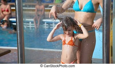 woman and girl taking a shower near water pool