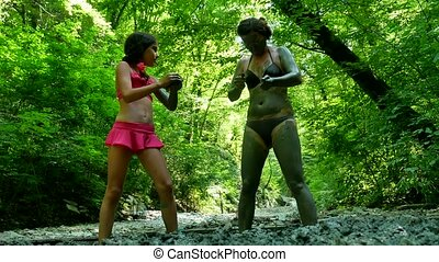 Woman and girl teen tourist in bathing suit is smeared with curative clay on the nature of mountain forest. girl skin treatment medicine