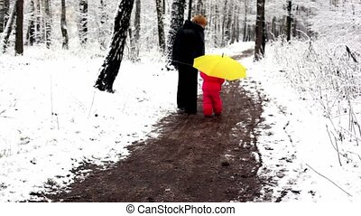 Woman and girl walking by pathway in snow-covered park holding hands
