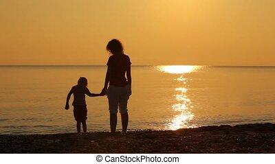 Woman and girl wetting feet in the sea