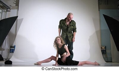 woman and  guy pose for photographer in studio