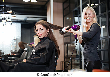 Woman and hairdresser with fan making hot styling at salon -...