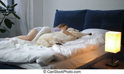 Woman and her best friend pet dog sleeping in bed - Adult...