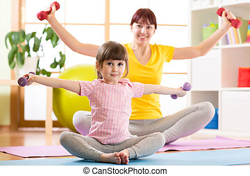 Woman and her child daughter doing fitness exercises with dumbbells together in gym