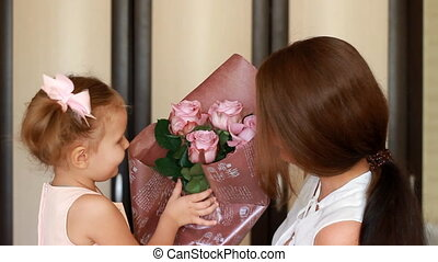 Woman and her child girl with a bouquet of roses smiling and...