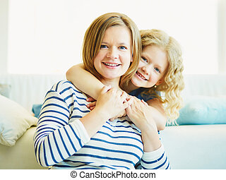 Woman and her child - Affectionate youthful girl embracing...