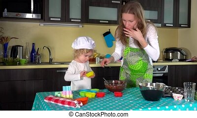 woman and her cute little daughter filling muffin cases -...