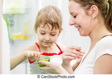 woman and her daughter applying cream on face in bathroom