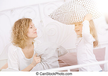 Woman and her daughter having pillow fight