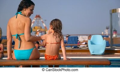woman and her daughter sits near waterpool