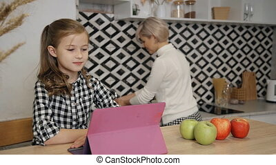 Woman and her daughter spending time together on kitchen -...