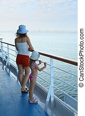 woman and her daughter standing on deck of cruise ship and looking away