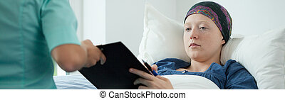 Woman and her diagnosis - Young woman with tumor lying in...